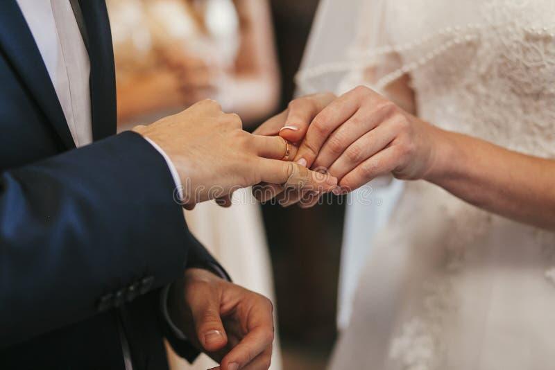 Manos hermosas de novia y del novio que intercambian los anillos de bodas en chur fotografía de archivo