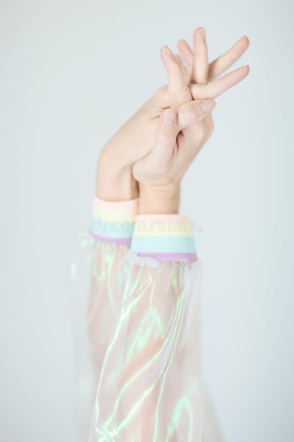 Manos hermosas y brazos de la mujer que llevan un suéter con el efecto olográfico, mirada plástica artificial de la vanguardia mo fotos de archivo
