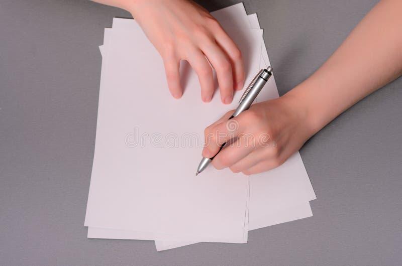 Manos humanas con la escritura del lápiz en el documento y el caucho del borrado sobre fondo de madera de la tabla imagenes de archivo