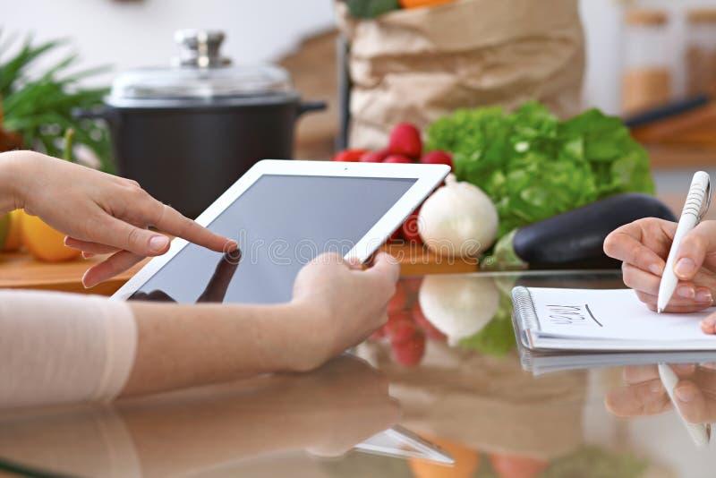 Manos humanas de dos personas femeninas que usan el panel táctil para hacer el menú en la cocina El primer de dos mujeres está ha imágenes de archivo libres de regalías