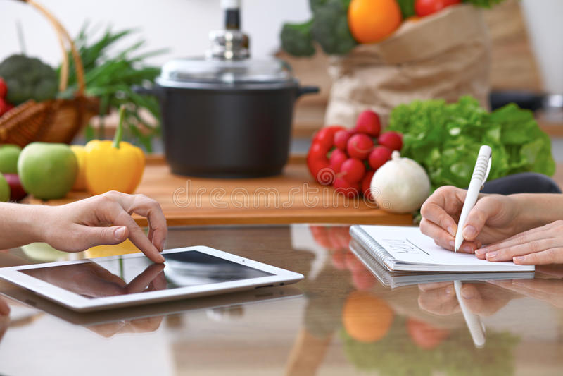 Manos humanas de dos personas femeninas que usan el panel táctil para hacer el menú en la cocina El primer de dos mujeres está ha imagenes de archivo
