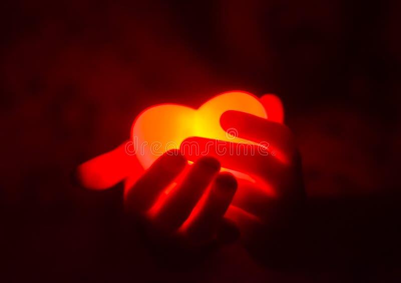 Manos humanas que llevan a cabo el corazón que brilla intensamente rojo en la oscuridad fotografía de archivo