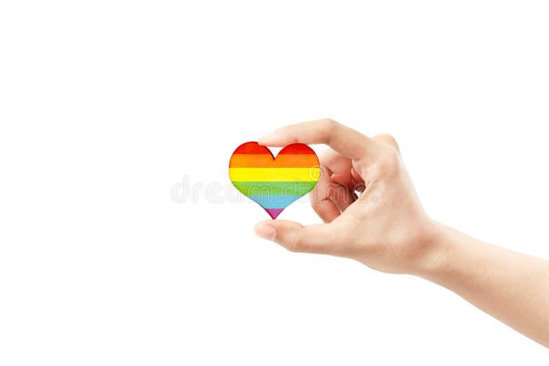 Manos humanas que muestran el corazón con la bandera del arco iris como símbolo de LGBT fotografía de archivo