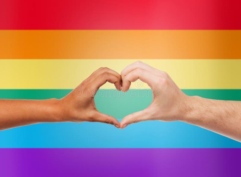 Manos humanas que muestran forma del corazón sobre el arco iris foto de archivo