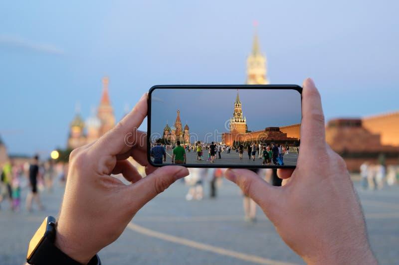 Manos humanas que sostienen el teléfono móvil, tomando una foto de los vagos del santo fotos de archivo libres de regalías
