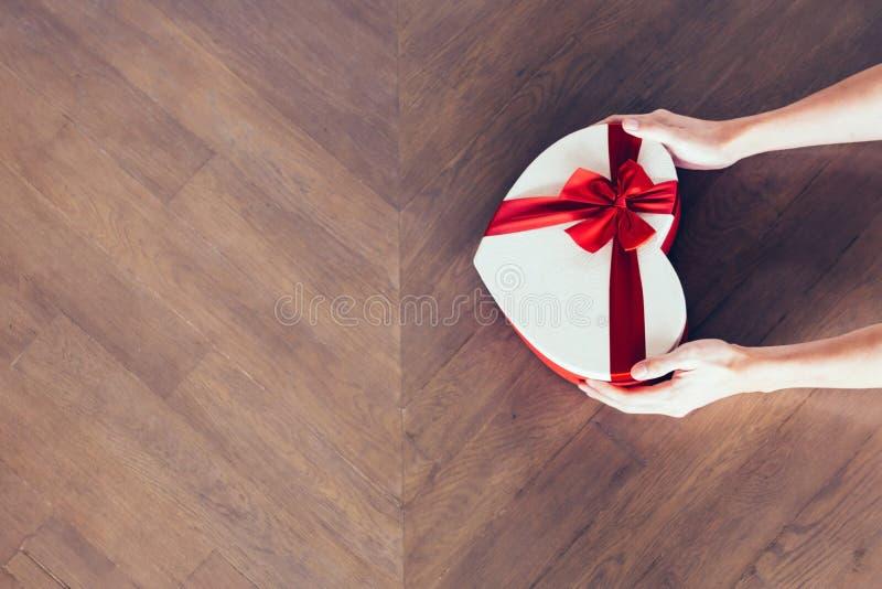 Manos humanas que sostienen un actual regalo con la cinta roja en fondo de madera - de la visión superior - con el espacio de la  fotos de archivo libres de regalías