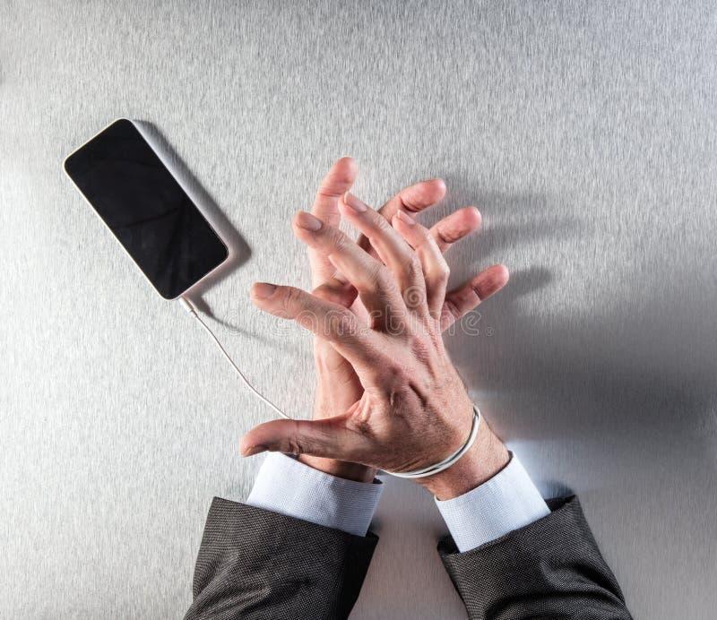Manos impacientes del hombre de negocios obsesionadas con dependencia móvil de la esclavitud y de la tecnología fotografía de archivo