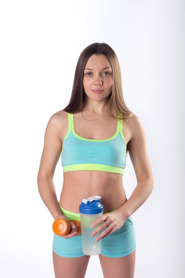Manos jovenes de la mujer de la aptitud con la botella y la pesa de gimnasia del deporte imagen de archivo libre de regalías