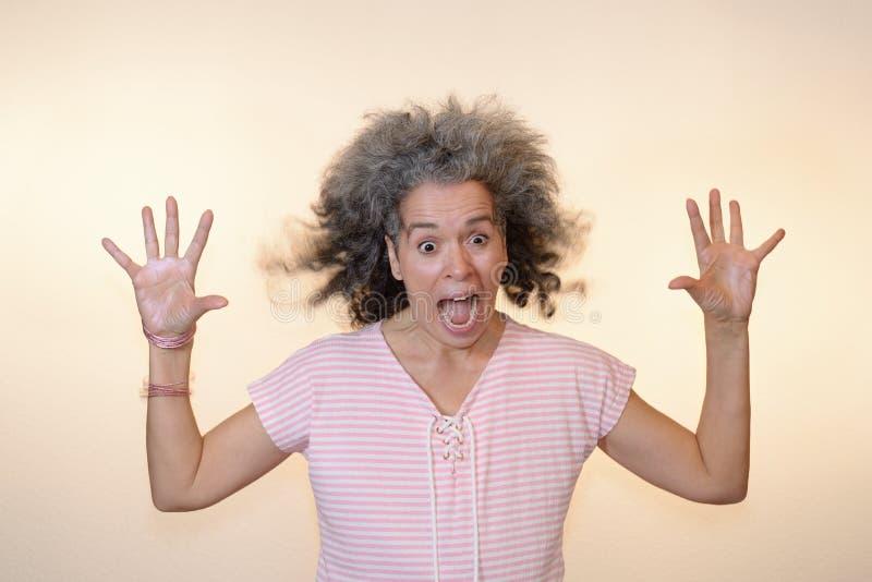 Manos maduras de griterío locas chocadas de la mujer para arriba foto de archivo libre de regalías