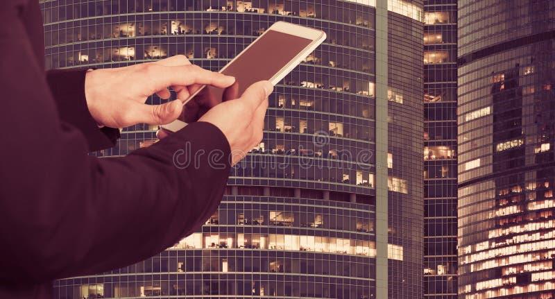 Manos masculinas con el teléfono en el fondo de la construcción fotografía de archivo libre de regalías