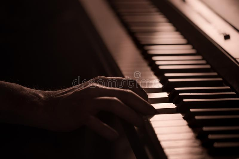 Manos masculinas en el primer de las llaves del piano de un fondo colorido hermoso imágenes de archivo libres de regalías