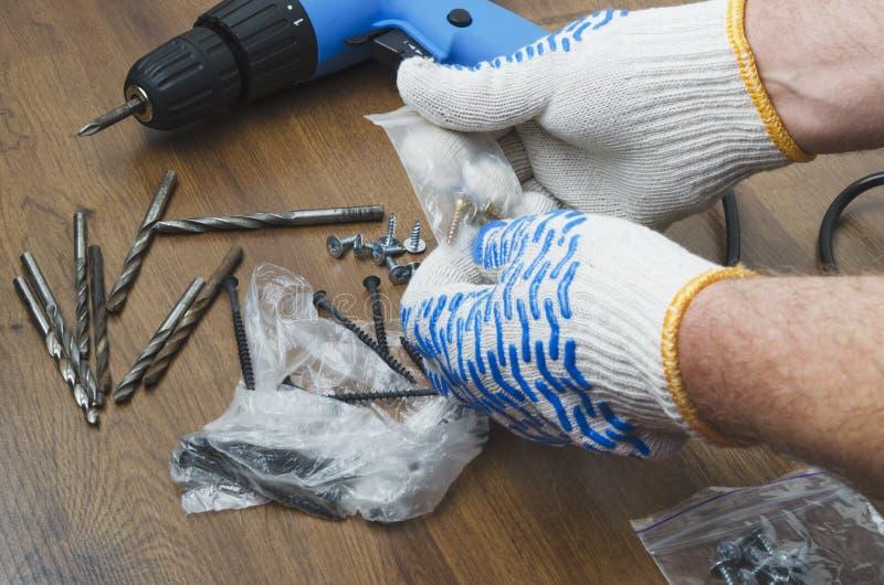 Manos masculinas en los guantes que eligen los tornillos para el destornillador Concepto de renovación en hogar imagenes de archivo