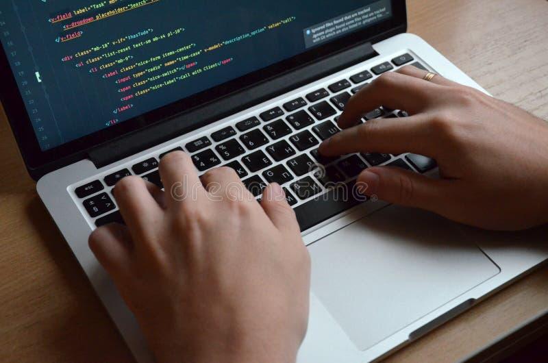Manos masculinas en un teclado negro Codificación europea en un ordenador S imágenes de archivo libres de regalías