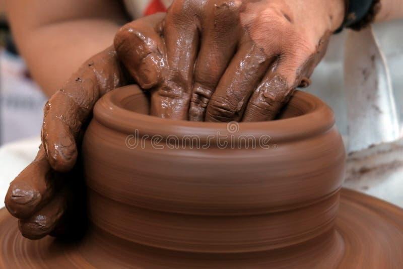 Manos masculinas o femeninas forman un cuenco en una rueda de cerámica Trabajar con arcilla roja Platos tradicionales a mano Prof fotografía de archivo