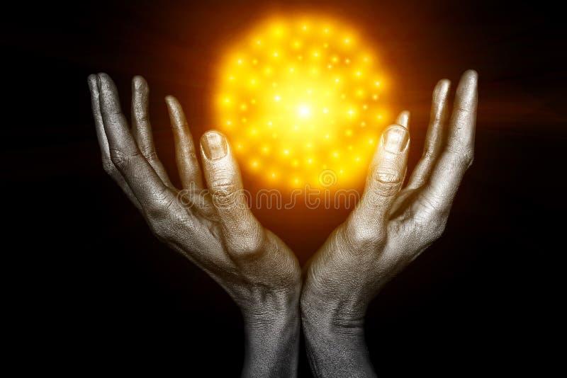 Manos masculinas plateadas con una bola amarilla de la energía imagen de archivo