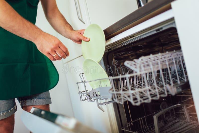 Manos masculinas que cargan platos sucios a la lavadora del plato fotografía de archivo libre de regalías