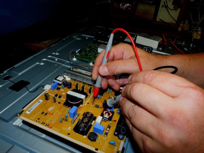 Manos masculinas que llevan a cabo el metro de voltio que repara la placa de circuito moderna de la TV fotografía de archivo libre de regalías
