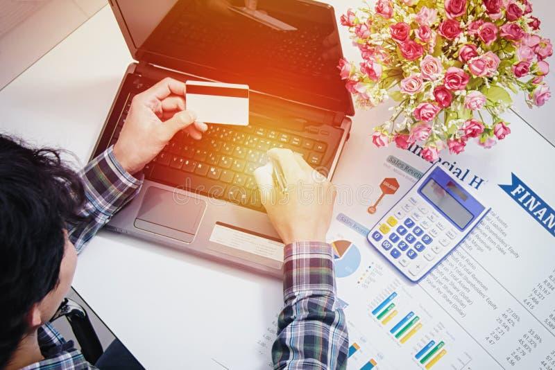 Manos masculinas que llevan a cabo números que mecanografían de la tarjeta de crédito en el teclado de ordenador: concepto en lín imagen de archivo