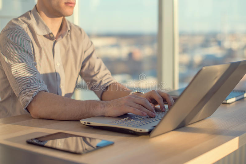 Manos masculinas que mecanografían, usando el ordenador portátil en oficina Diseñador que trabaja en el lugar de trabajo fotos de archivo