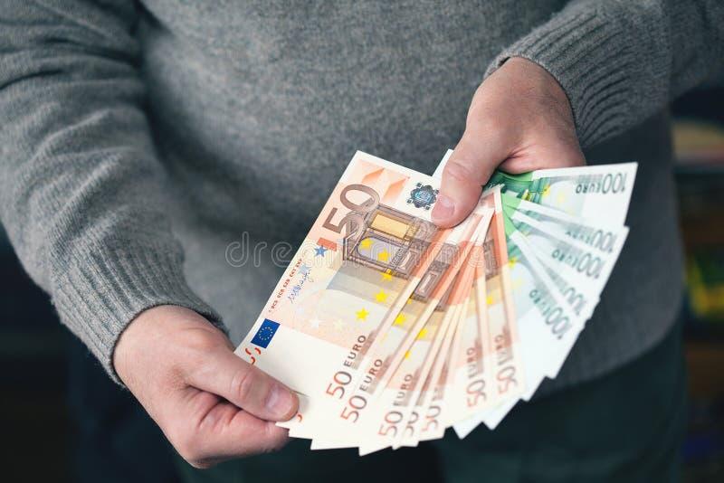 Manos masculinas que sostienen el dinero bajo la forma de fan Dinero, moneda euro fotos de archivo