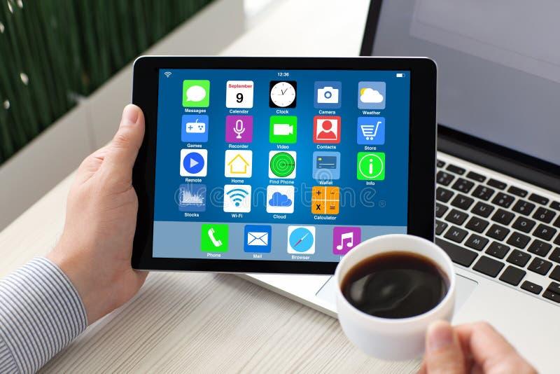 Manos masculinas que sostienen la tableta con los apps de los iconos de la pantalla de inicio imagenes de archivo