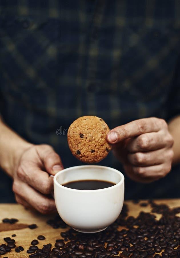 Manos masculinas que sostienen la taza de la galleta y de café foto de archivo