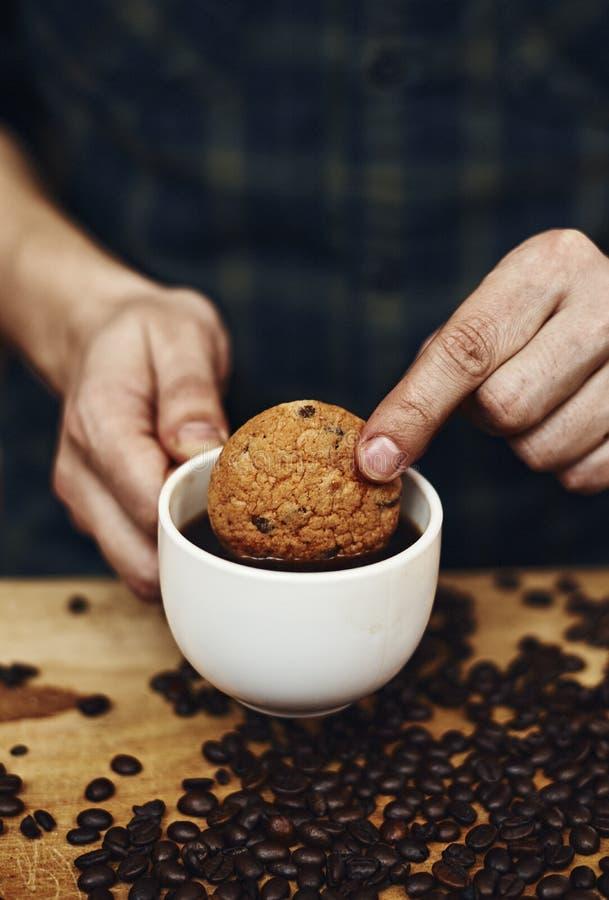 Manos masculinas que sostienen la taza de la galleta y de café imagen de archivo