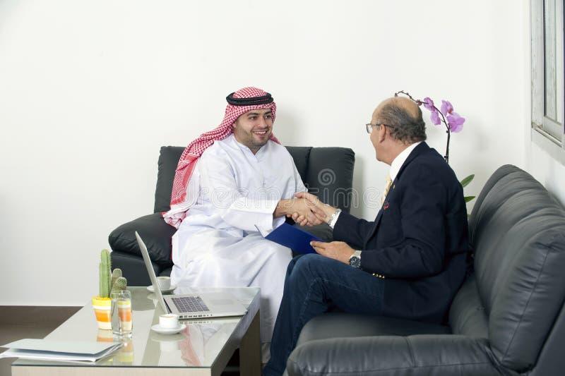 Manos mayores de Shaking del hombre de negocios con el hombre de negocios árabe fotografía de archivo