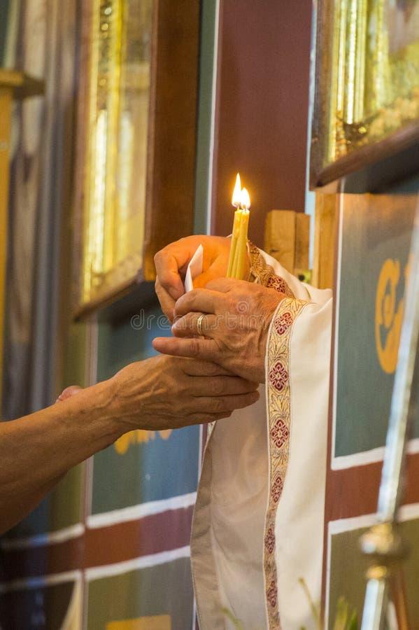 Manos mayores del sacerdote que dan velas a una señora mayor fotografía de archivo libre de regalías