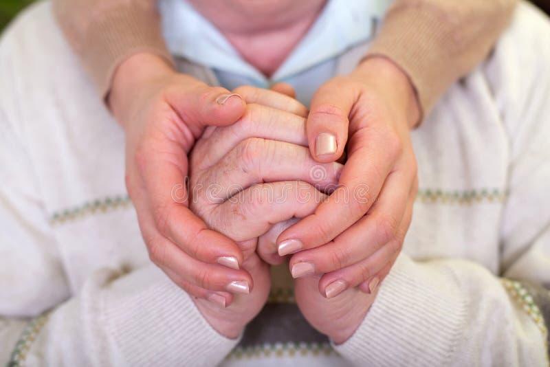 Manos mayores y manos jovenes del ` s del cuidador imagenes de archivo