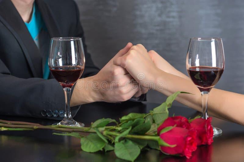 Manos modernas de los pares en la tabla del restaurante con dos vidrios de vino tinto y de rosas foto de archivo libre de regalías