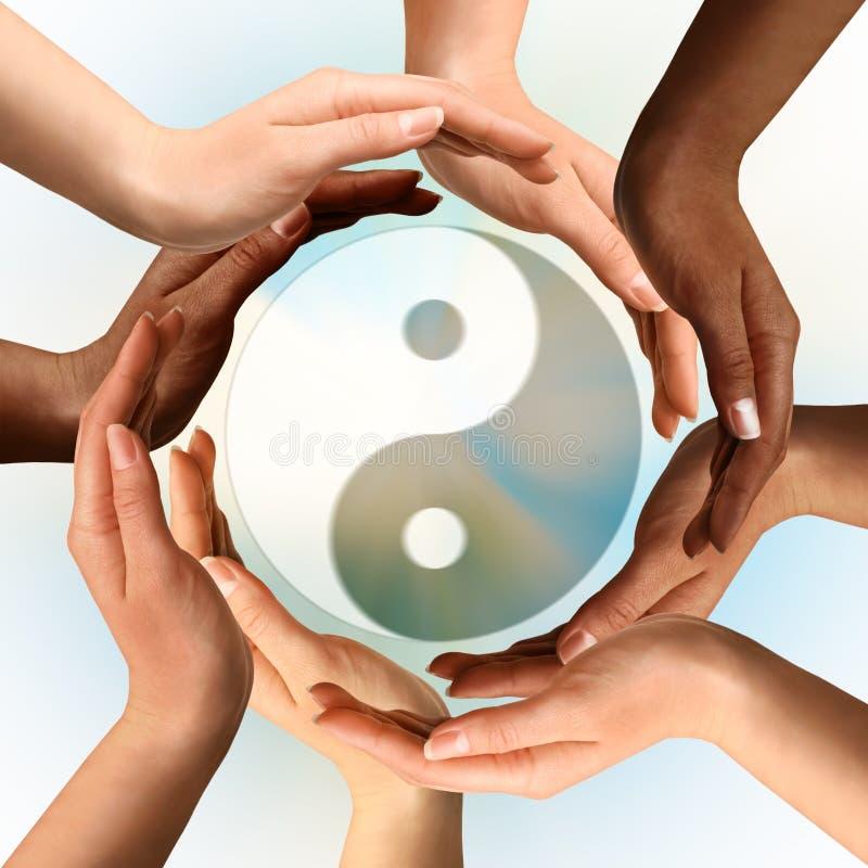 Manos multirraciales que rodean el símbolo de Yin Yang foto de archivo