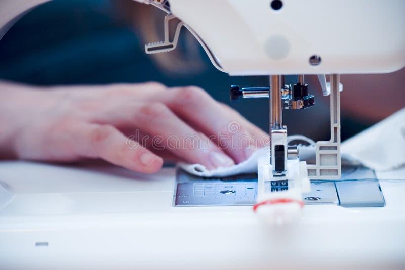 Manos ocupadas en la máquina de coser. foto de archivo