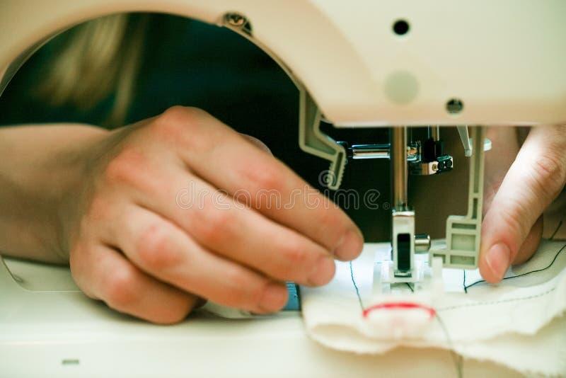 Manos ocupadas en la máquina de coser.   foto de archivo libre de regalías