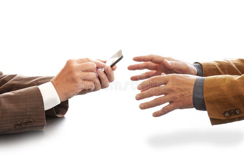 Manos a partir de dos hombres de negocios en la conversación por un escritorio Uno que manda un SMS en un teléfono celular Negoci imagenes de archivo
