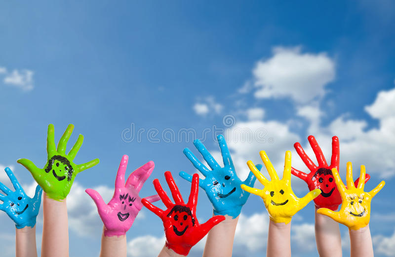 Manos pintadas coloridas con smiley imagen de archivo