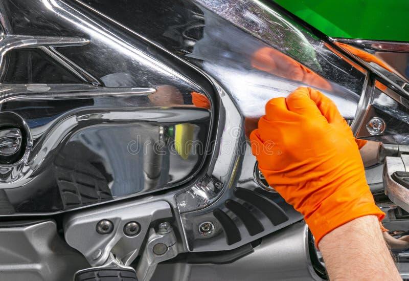 Manos polacas del trabajador de la cera del coche que aplican la cinta protectora antes de pulir Motocicleta que pulimenta y de p foto de archivo libre de regalías