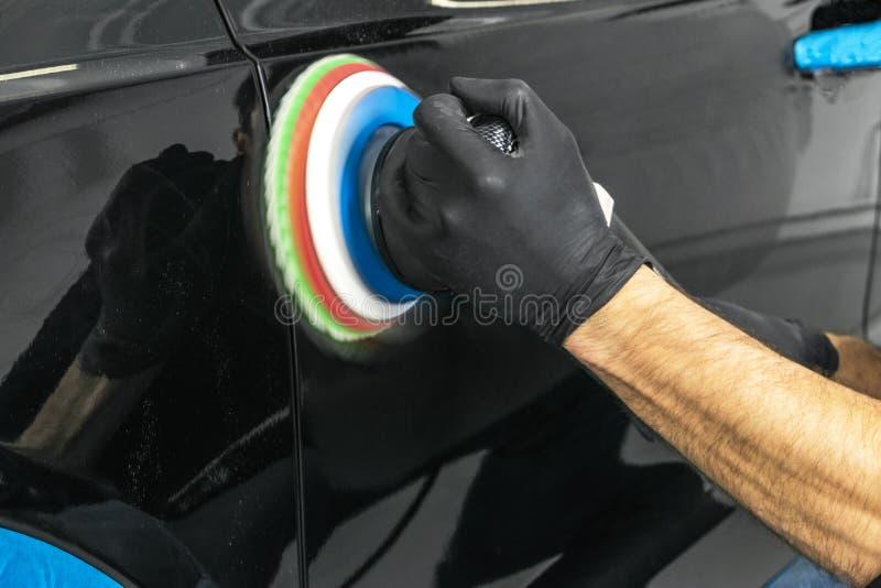 Manos polacas del trabajador de la cera del coche que aplican la cinta protectora antes de pulir Coche que pulimenta y de pulido  fotografía de archivo