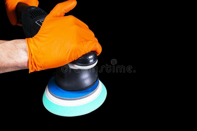 Manos polacas del trabajador de la cera del coche que aplican la cinta protectora antes de pulir Coche que pulimenta y de pulido  imagen de archivo libre de regalías