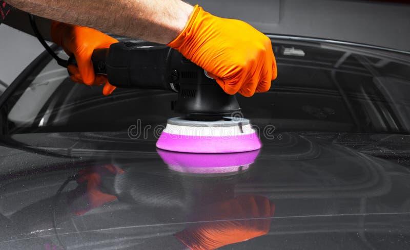 Manos polacas del trabajador de la cera del coche que aplican la cinta protectora antes de pulir Coche que pulimenta y de pulido  imagen de archivo