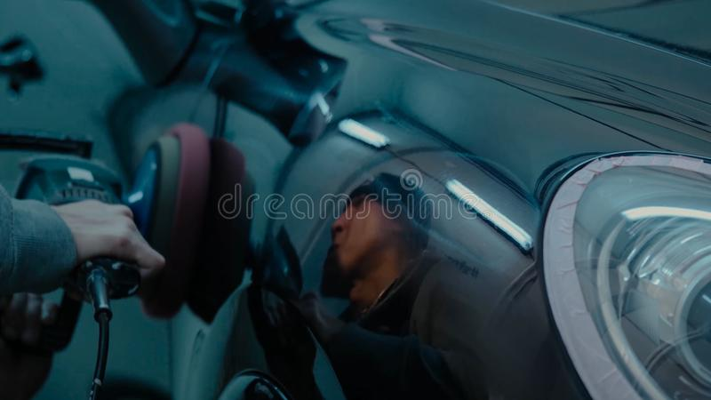 Manos polacas del trabajador de la cera del coche que aplican la cinta protectora antes de pulir Coche que pulimenta y de pulido  fotografía de archivo libre de regalías