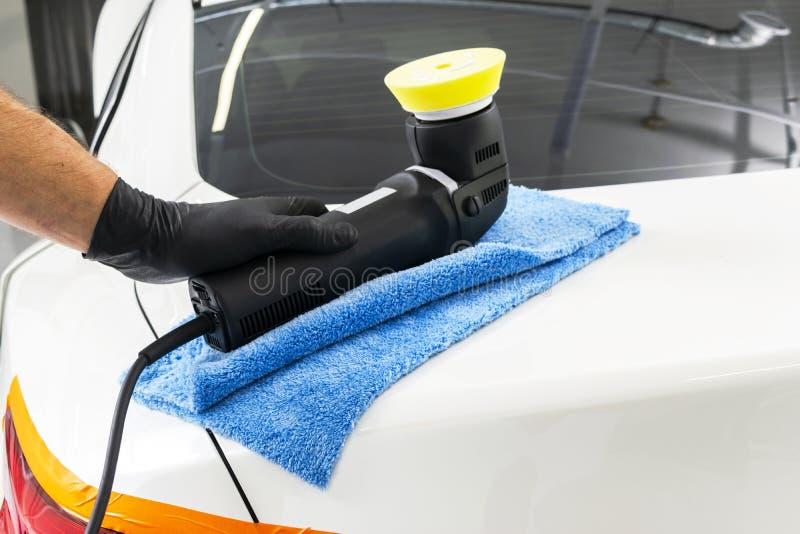 Manos polacas del trabajador de la cera del coche que llevan a cabo el pulidor y el pulimento Cierre encima del pulidor a mano de imagenes de archivo