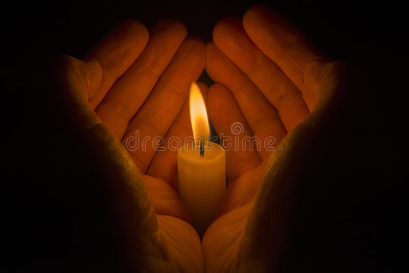 Manos protectoras alrededor de una vela ardiente imagen de archivo