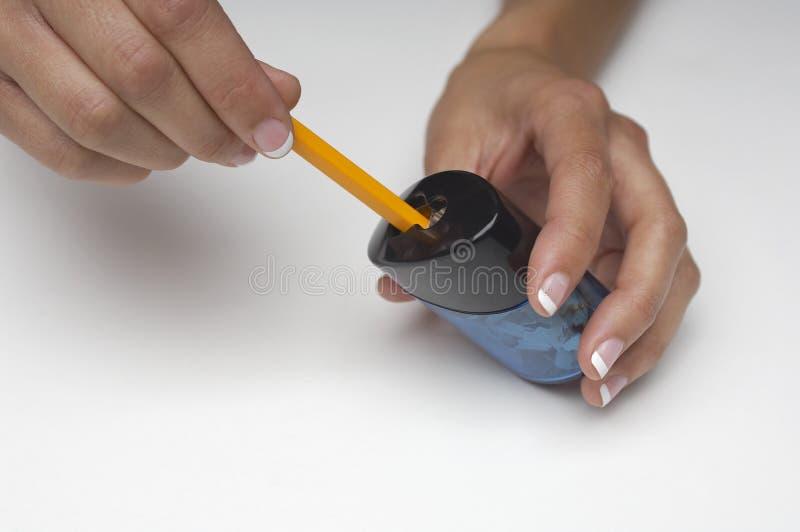 Manos que afilan el lápiz fotografía de archivo