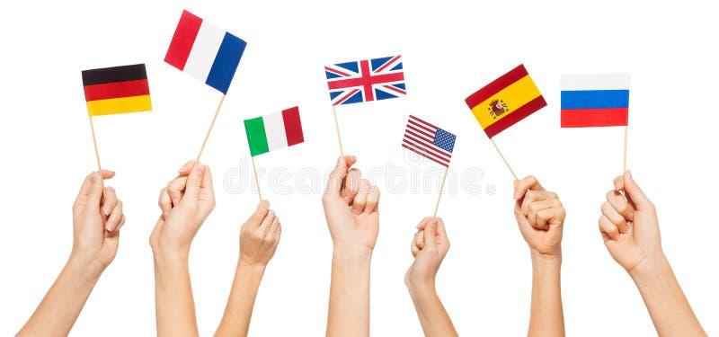 Manos que agitan banderas de los Estados miembro de los E.E.U.U. y de la UE fotos de archivo