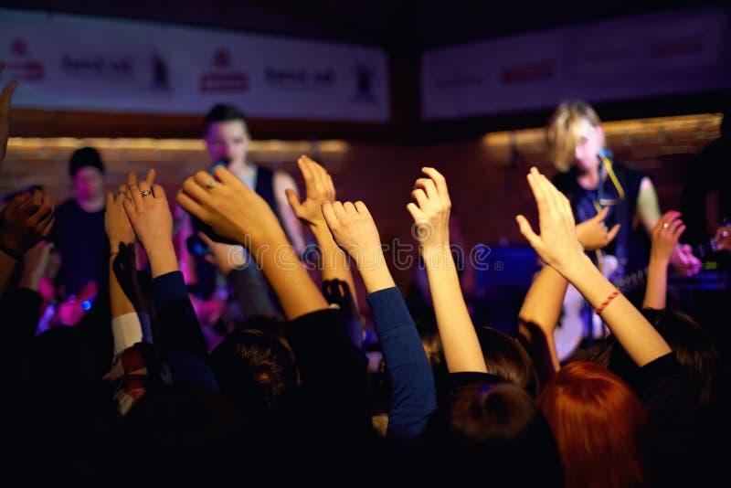 Manos que agitan de la juventud en concierto en club de noche foto de archivo