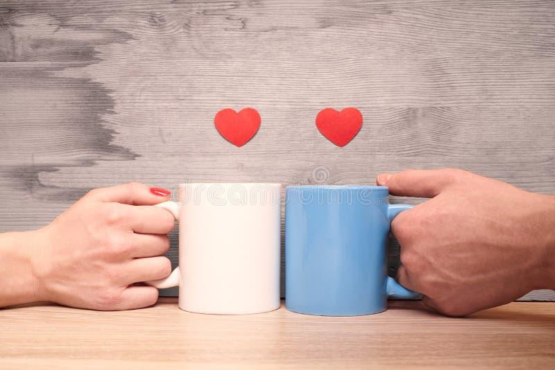 Manos que aman los pares que sostienen las tazas con los corazones foto de archivo