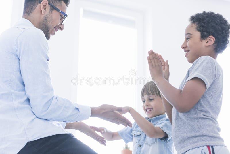 Manos que aplauden felices del juego de niños imagen de archivo