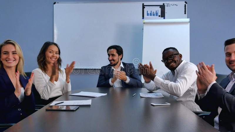 Manos que aplauden satisfechas del equipo orgulloso del negocio y mirada de la cámara en una oficina moderna foto de archivo