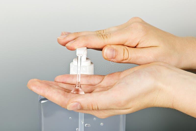 Manos que aplican el gel del desinfectante fotografía de archivo libre de regalías